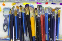 Many art brushes lie on the palette, paints. Many art brushes lie on the palette, colored paints Royalty Free Stock Photo