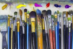 Many art brushes lie on the palette, colored paints. Brushes for painting and colored oil paints lie on palette in the artist`s studio vector illustration