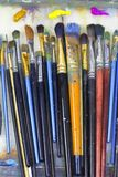 Brushes for painting and colored oil paints lie on palette in the artist`s studio. Many art brushes lie on the palette, colored paints Royalty Free Stock Photography