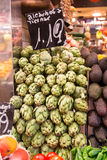 Many artichokes on a market stall Stock Photo