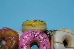 Assorted donuts on a blue background. Many Assorted donuts on a blue background royalty free stock photography
