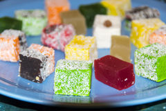 Many assorted multicolored Turkish Delight on blue background royalty free stock images