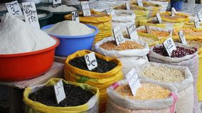 Many bags with different cereals on which hang the price tags stand on the market stock video footage