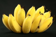 Many bananas on black background. Fresh Bunch of Organic ripe bananas Royalty Free Stock Images