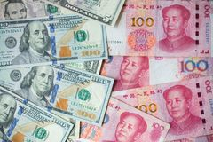 The many banknote. money hundred dollars bills. Pile of various currencies  on yuan background.Closeup of assorted American banknotes. war of currency.war of Stock Photography