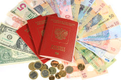 Many banknotes of different countries and the passport for travel. Many banknotes and passports.Many banknotes of different countries and the passport for Stock Photos