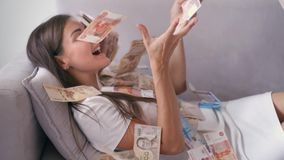 Many banknotes fly in the air overhead in slow motion. A girl lies and a lot of money falls on her. happy woman rejoices. Huge wealth of money stock footage