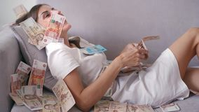 Many banknotes fly in the air overhead in slow motion. A girl lies and a lot of money falls on her. happy woman rejoices. Huge wealth of money stock video