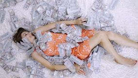 Many banknotes fly in the air overhead in slow motion. A girl lies and a lot of money falls on her. happy woman rejoices. Huge wealth of money, slow motion stock video footage