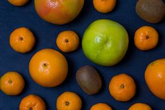 Many beautiful bright juicy ripe delicious mouth-watering citrus fruits are are dark blue on a black background scattered freely stock photo