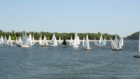 Many beautiful floating sail yachts medium size with crew , on the Dnieper River. stock footage