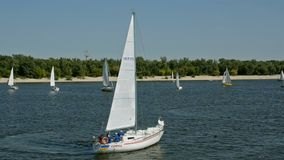 Many beautiful floating sail yachts medium size with crew , on the Dnieper River. stock video