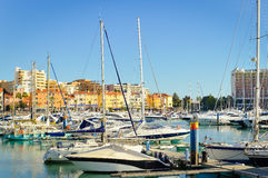 Many beautiful luxury yachts mooring in sunny. Picture of many beautiful yachts mooring in harbour. Sunny day in port with luxury boats on summer blue sky Stock Images