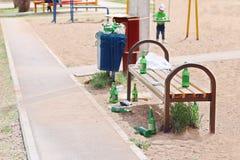 Many beer bottles near bench on children playground Stock Photo