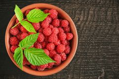 Many berries of red raspberries in a clay bowl on a rustic wooden table.  Stock Image
