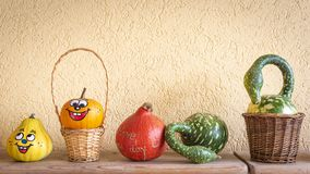 Many big and small pumpkins with and without face. Before a yellow wall royalty free stock photo
