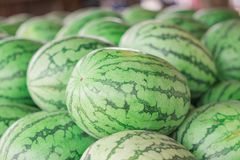 Many big sweet green watermelons and one cut watermelon.  stock photo