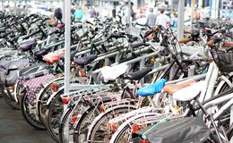 Many bikes parked, people blurred Stock Photos
