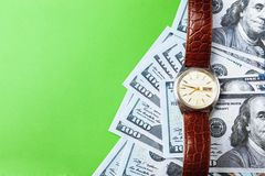 Many bills of 100 dollars, us banknote, green background with money cash currency close-up, concept time worth money, clock. Many bills of 100 dollars, us Stock Photography