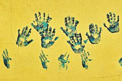 Hand prints on a bright yellow concrete wall stock images