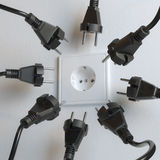 Many Black Electric Plugs are Fighting for Power from the Wall Socket Stock Images