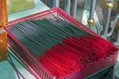 Many black incense sticks in a red basket Royalty Free Stock Images