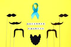 Many black paper Mustache on yellow background. Beard and mustache blue ribbon on yellow background. stock images