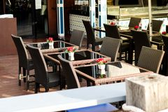 Many black rattan chairs with red rose in vase and clear table. Set on wooden floor at restaurant for street food background or texture - outdoor concept Stock Image