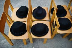 Many black retro hats lie on wooden chairs stock images