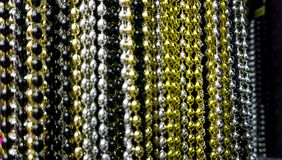 Many black, white, silver, gold and golden beads party neacklaces for New Years celebrations or background. Macro close. Many black, white, silver, gold and royalty free stock photo