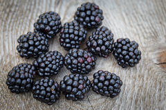 Many blackberries resting on table Royalty Free Stock Images
