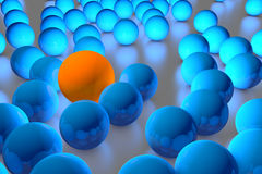 Many blue balls among which the orange stands out Royalty Free Stock Image