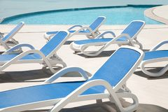 Many blue chaise lounge by the pool. Resort spa concept royalty free stock photography