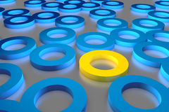 Many blue cylinder discs among which the yellow one stands out Stock Photos