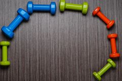 Many blue green and one orange in the middle dumbbells on a background ,concept preparing to fitness sports equipment top view moc stock photography