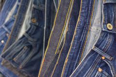 Many blue jeans on the rack background. Store stock photo