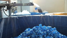 Many blue plastic bottle caps fall from conveyor stock video footage