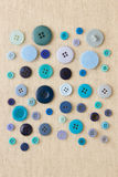 Blue individual buttons on hessian. Many blue sewing or clothing buttons on hessian royalty free stock photo
