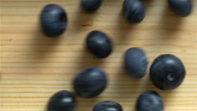 Many blueberries rolling on wooden surface. Slow motion. Top View. stock footage