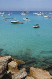 Many boats moored on the blue and green sea near the rocks Stock Photography