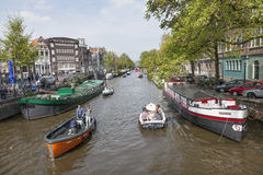 Many boats ride on canal in amsterdam on a sunny day in spring Royalty Free Stock Photos