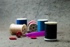 Many bobbin of thread with needle and button Royalty Free Stock Photo
