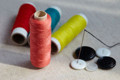 Many bobbin of thread with needle and buttons Royalty Free Stock Photos