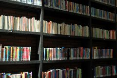 Books in different colours on the shelves in the library. Many books in different colours on the shelves, some in the sun or shadow in a part of the municipal Stock Photos