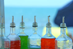 Many bottles of colored syrup for preparing ice creams on the be Stock Photos