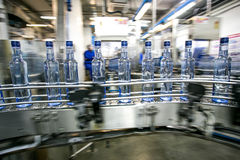 Many bottles on conveyor belt. In factory, production of russian traditional alcohol drink vodka Stock Images