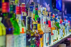 Many bottles of different alcohol by barrels Royalty Free Stock Images