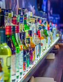 Many bottles of different alcohol by barrels Stock Images