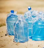 Many bottles of water standing in the sand. A bottle of water standing in sand at the beach royalty free stock photo
