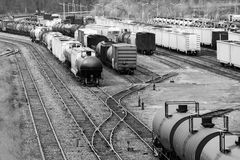 Many boxcars and cargo shipping train cars on tracks in a busy t. Rainyard, in black and white Stock Photo